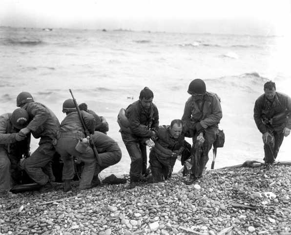Members of a landing party help injured Soldiers to safety on Utah Beach during the Allied Invasion of Europe on D-Day, June 6, 1944.