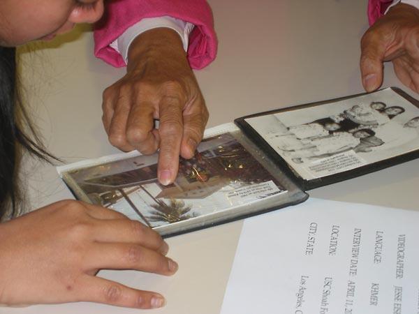 Survivor Phansy Peang shows Fatily Sa (left) family photos.
