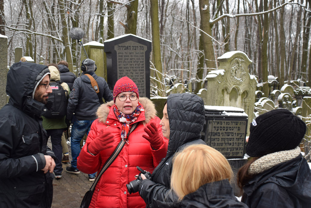 Teachers and students – including instructors Adam Musial of Krakow, left, and Johanna Söderholm from Finland, center – visit a Jewish cemetery in Warsaw. (USC Photo/Josh Grossberg)