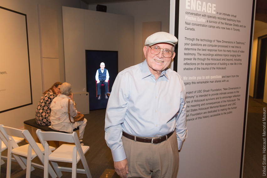 Pinchas Gutter near a display of his interview for New Dimensions in Testimony
