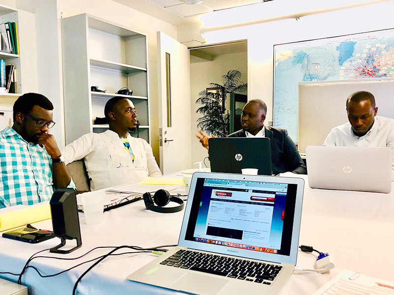 Members of the education team from Aegis Trust discuss creating IWitness activities that feature the testimonies from survivors and witnesses to the Genocide against the Tutsi in Rwanda. From left to right: Enoch Ssemuwemba, Pierre Claver Irakoze, Jean Nepo Ndahimana and Marc Gwamaka.