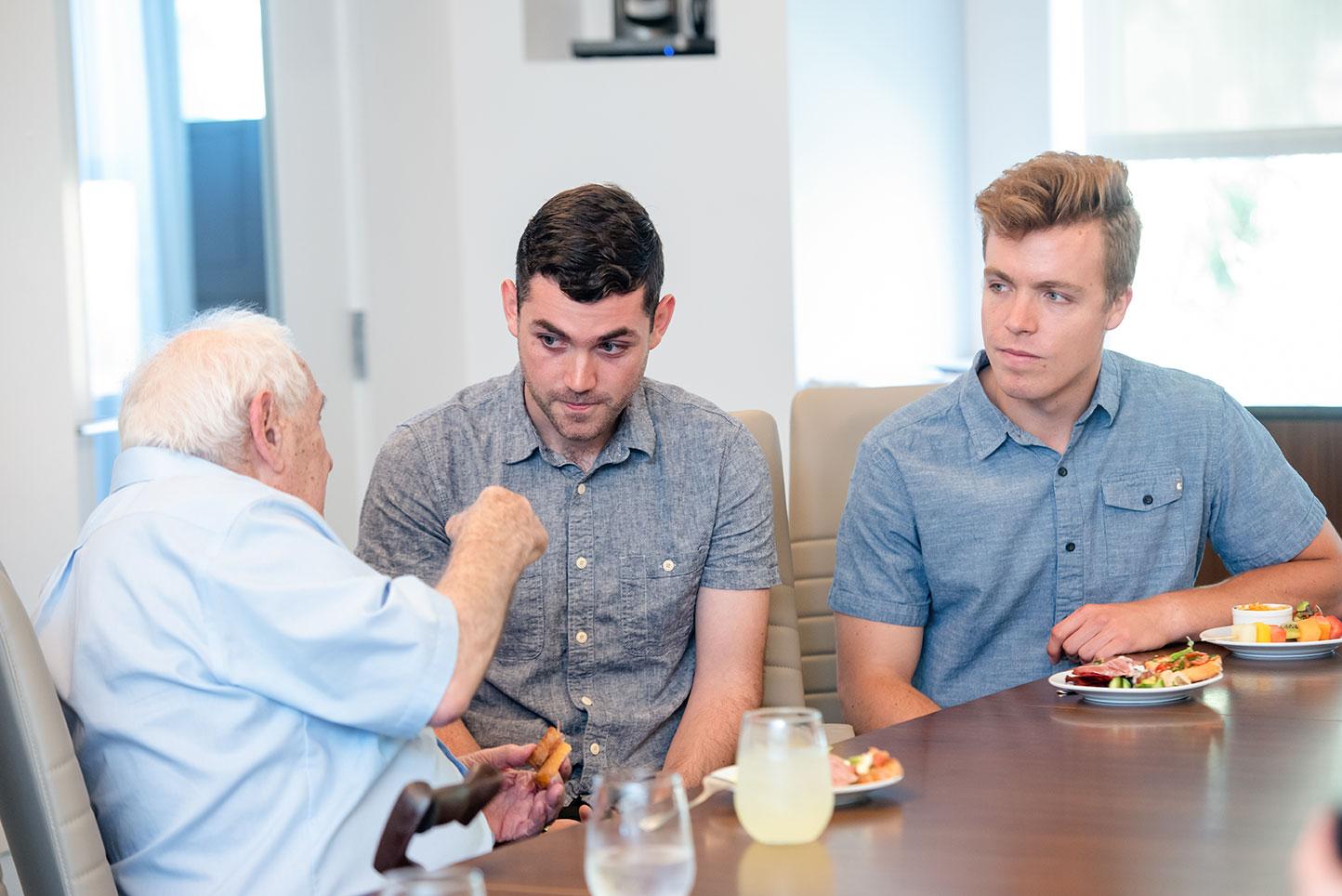 George Weiss speaking with former interns Alex Biniaz-Harris and Ambrose Soehn
