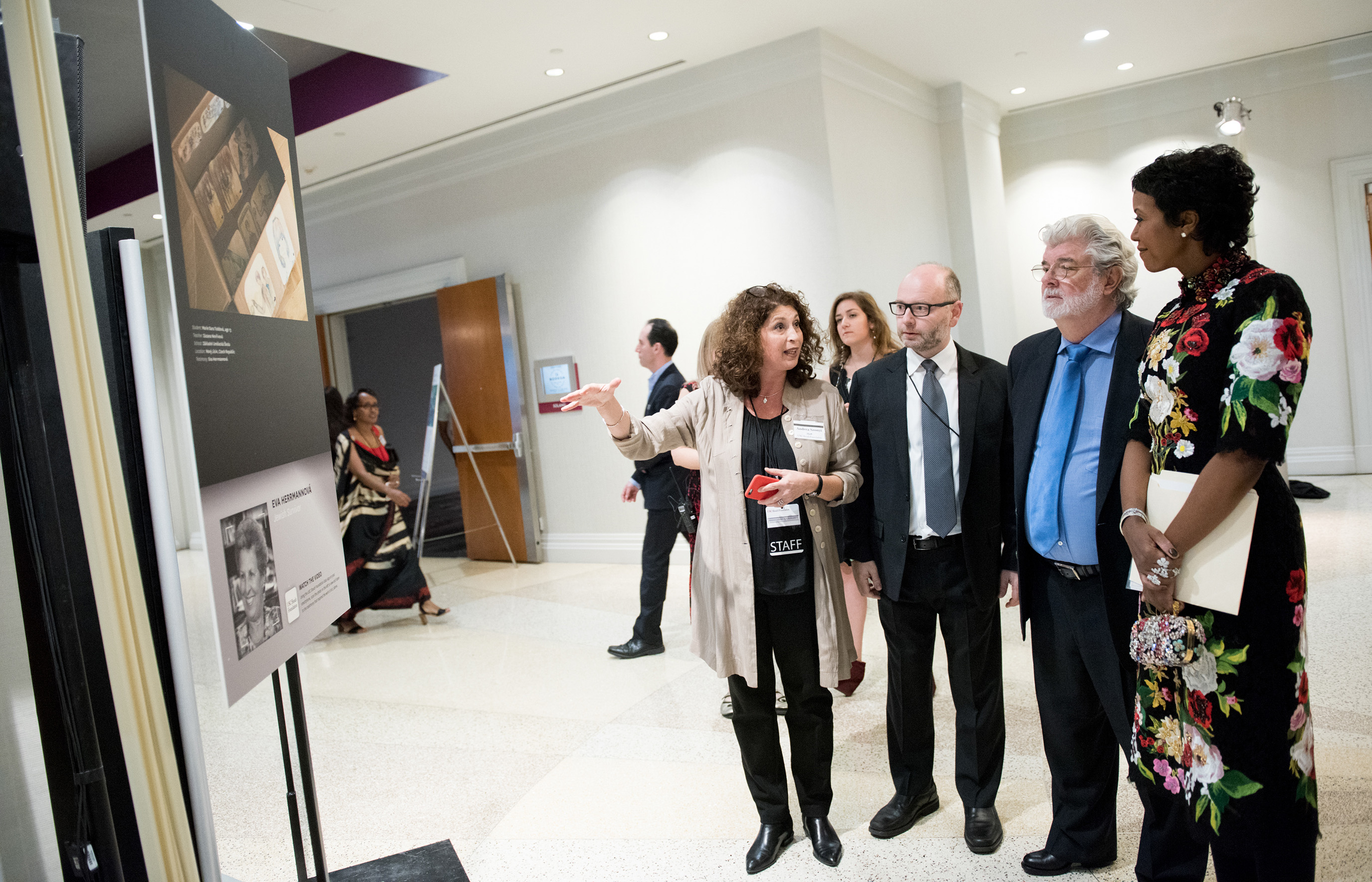 Andrea Szonyi shows the artwork to Stephen Smith, George Lucas and Mellody Hobson