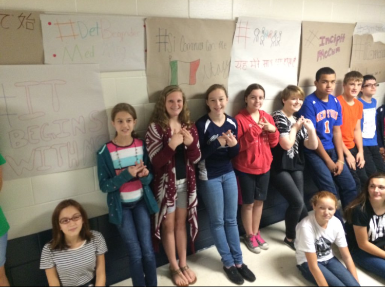 Students from Lauren Fenech and Steffanie Grotz's class in front of their student constructed #BeginsWithMe banners, written in the 10 most popular languages around the world.