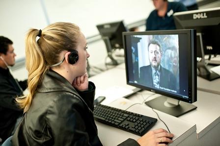 A teacher watches the testimony of Ellis Lewin, a Jewish Holocaust survivor.