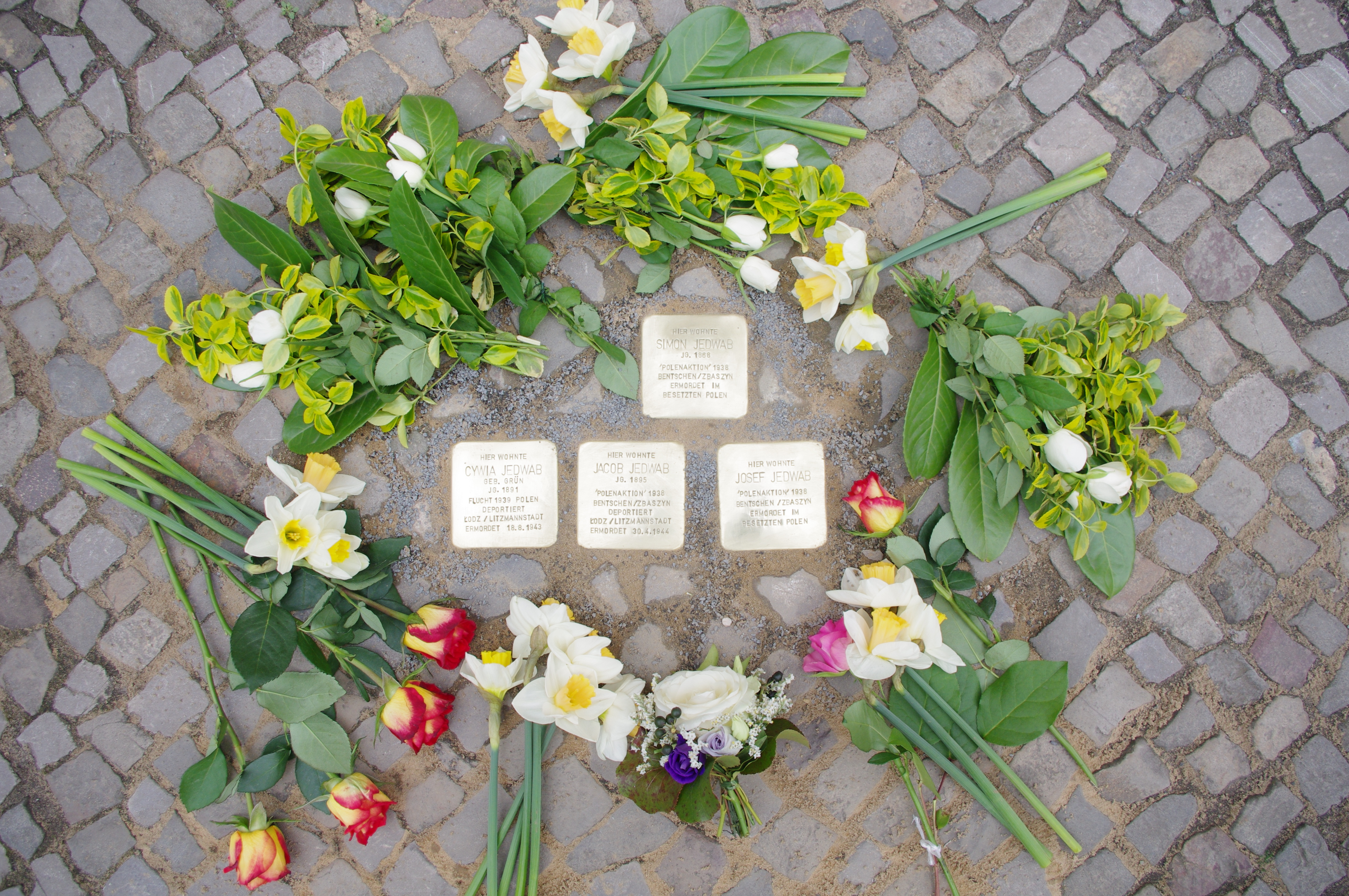 All four new stumbling stones with flowers at the end of the ceremony.