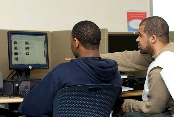 Michael Bolds, educational consultant, works with a student on his media project.