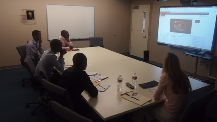 Director of Research and Documenation, Karen Jungblut (right), shows the interns a Holocaust survivor's testimony.