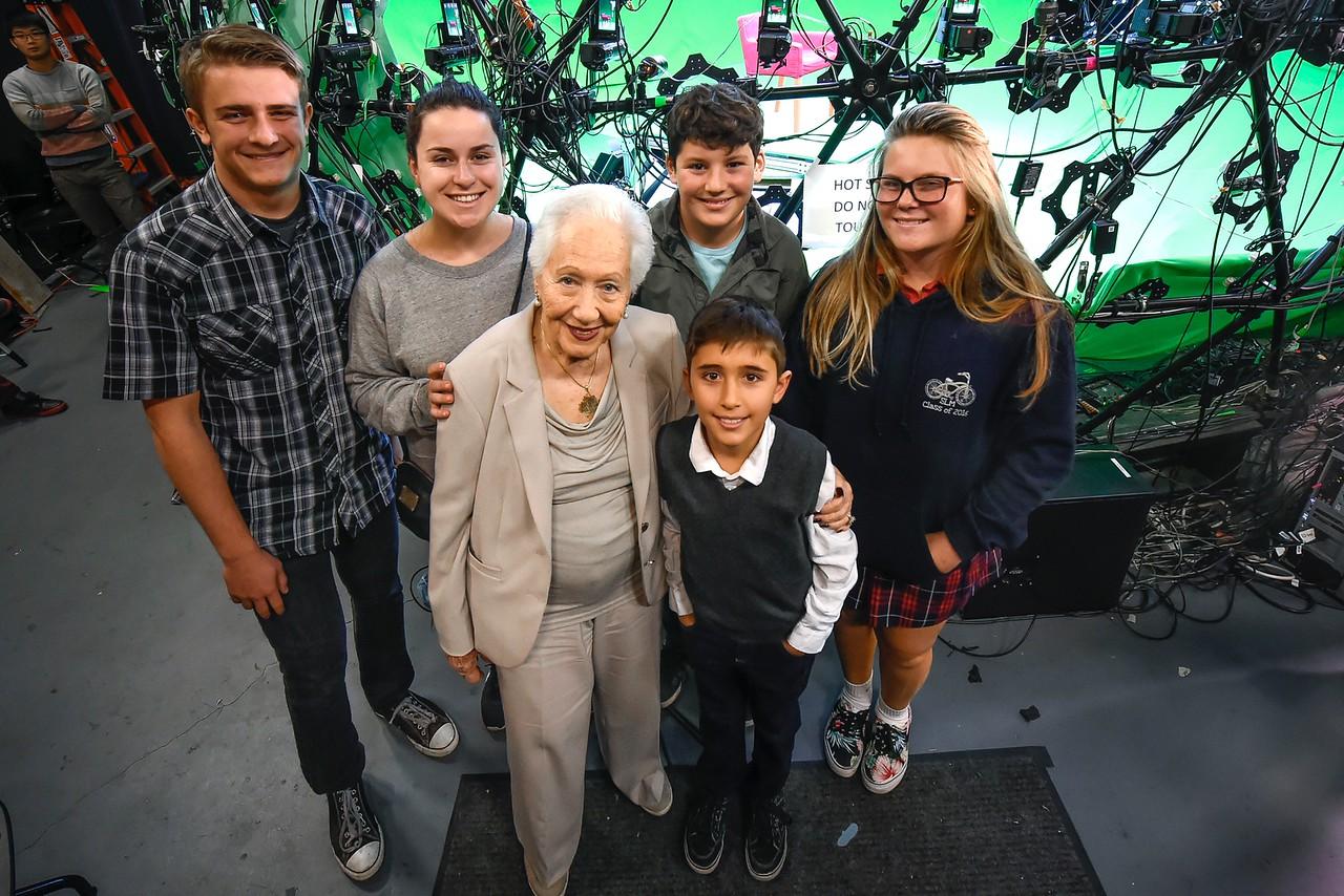 Renée Firestone posing with students during filming