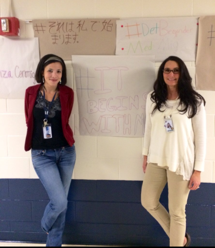 Educators Lauren Fenech and Steffanie Grotz in front of their students #BeginsWithMe banners.