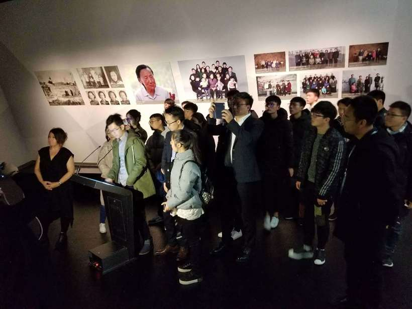 Students gather around as New Dimensions in Testimony Mandarin Project Assistant, Cheng Fang demonstrates interactive testimony, with creator and producer, Heather Maio-Smith, at the Nanjing Massacre Memorial 13 December 2017.