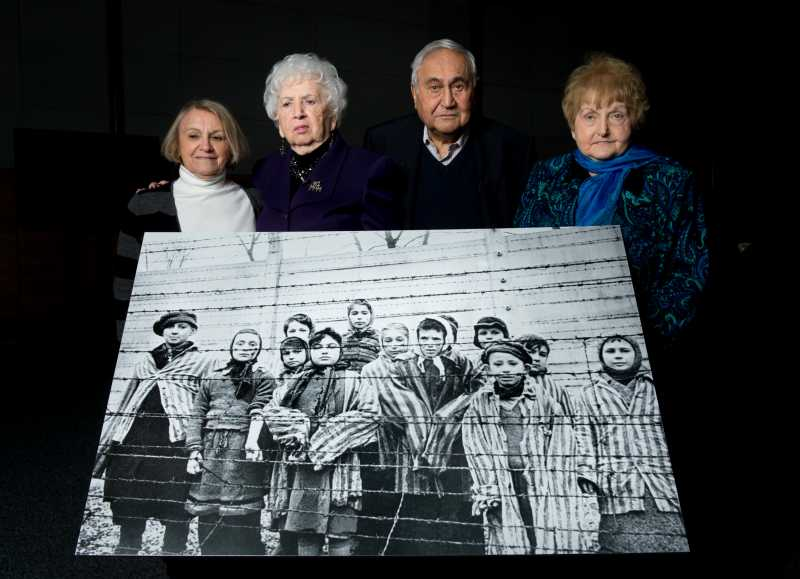(L-R) Paula Lebovics, Miriam Ziegler, Gabor Hirsch and Eva Kor pose with the original image of them as children taken at Auschwitz at the time of its liberation on January 26, 2015 in Krakow, Poland.