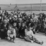 A group of Gypsy prisoners, awaiting instructions from their German captors, sit in an open area near the fence in the Belzec concentration camp.  Belzec, 1940 © USHMM, courtesy of Archiwum Dokumentacji Mechanicznej.