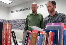 Lynn Sipe,  and Dan Leshem, associate director of research, review books on the Armenian Genocide for the library's new collection.